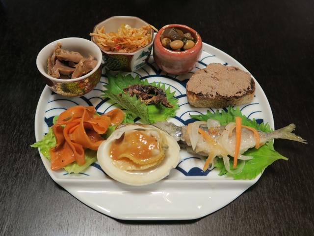 左手前から時計回りに、ニンジンのマリネ、砂肝、鳥とネギの和え物、煮豆、レバーペースト、アジの南蛮漬け、ホンビノス貝の酢味噌和え、中央はホタルイカの干物